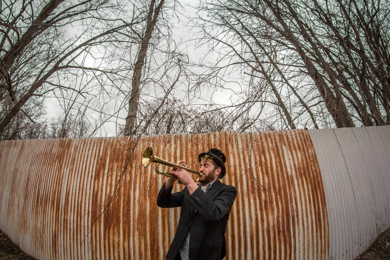Gypsy Trumpet Musician. Stylish bearded gypsy plays trumpet by rusty fence stock photos