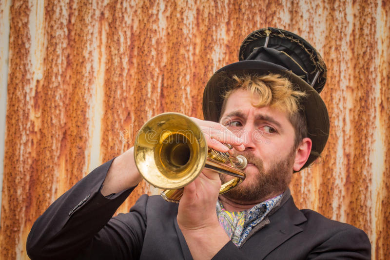 Gypsy Trumpet Musician. Stylish bearded gypsy plays trumpet by rusty fence royalty free stock images