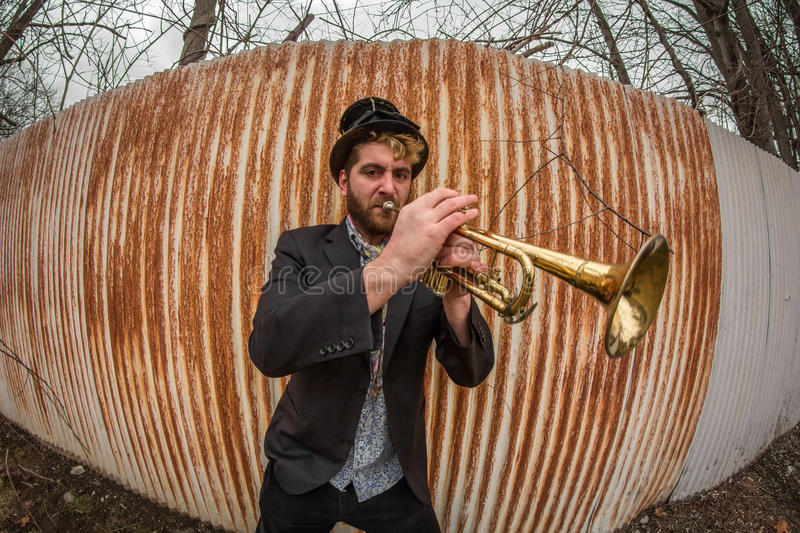 Gypsy Trumpet Musician. Stylish bearded gypsy plays trumpet by rusty fence royalty free stock photography