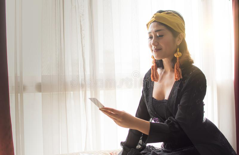 A gypsy woman is reading tarot card in room royalty free stock photography