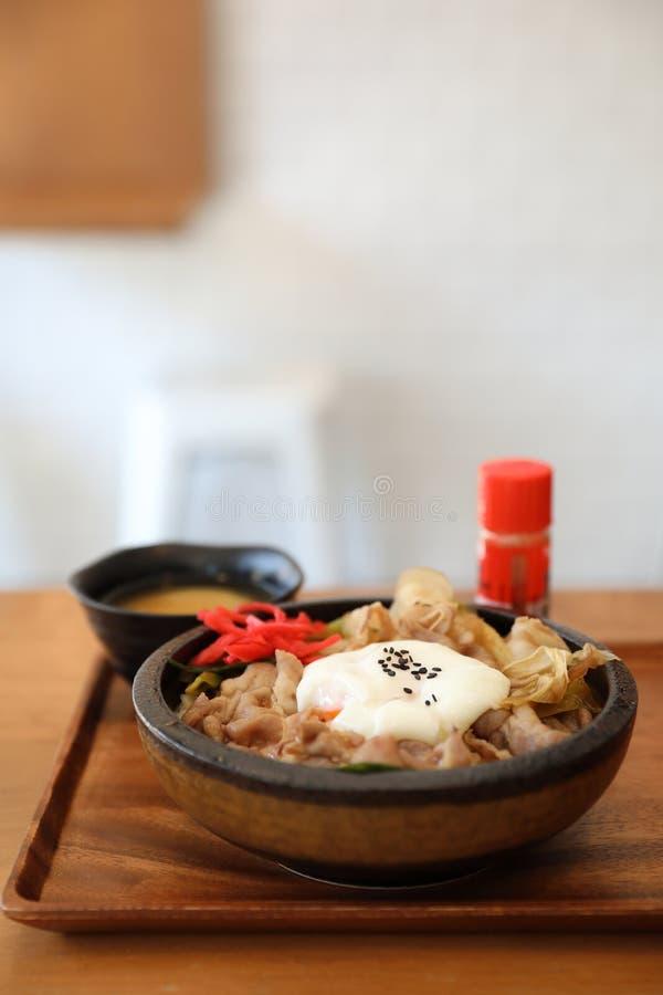 Gyudon för japansk mat överträffade japanskt nötkött på risbunken med ägget på trämagasinet arkivbild