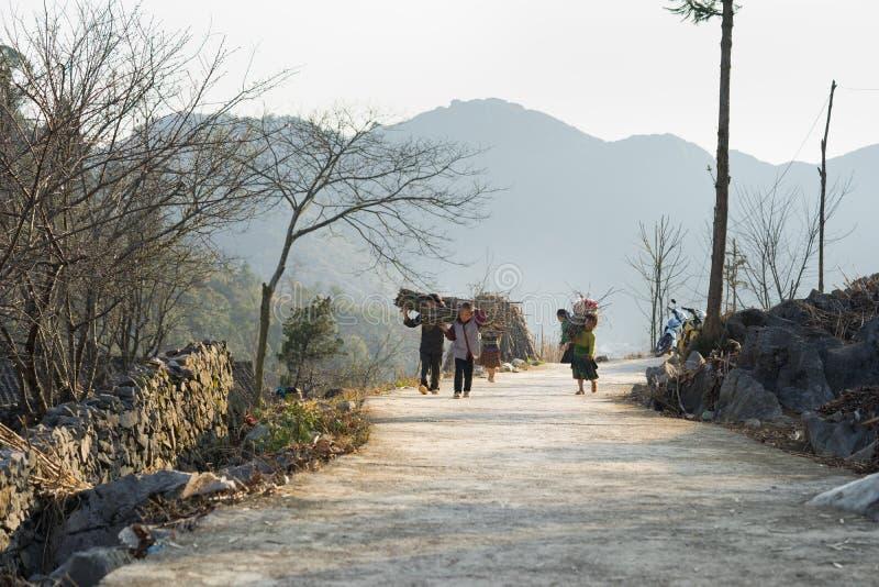 Hà Giang, Vietnam - 14. Februar 2016: Hà Giang Bergblick mit Kindern tragen Holz auf der Rückseite, die nach Hause auf Straße vor lizenzfreies stockbild