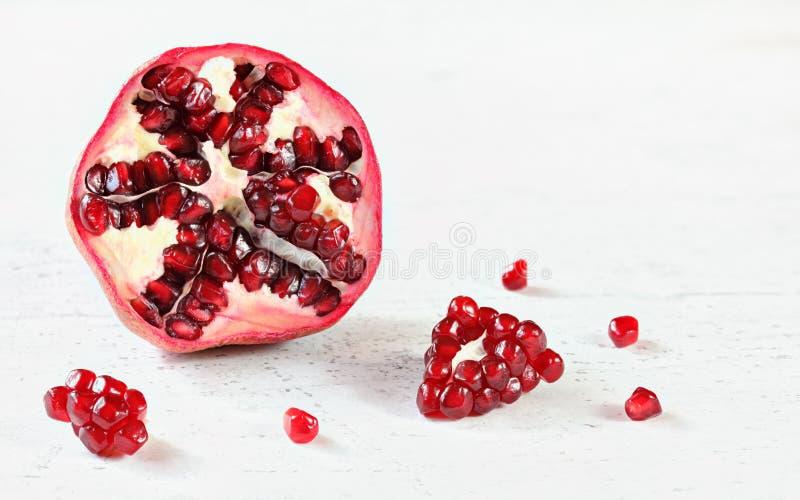 Hälfte des Granatapfels mit irgendeinem kleinem Edelstein wie den Früchten zerstreut auf weißes Brett Raum für Text in der oberen stockfotos