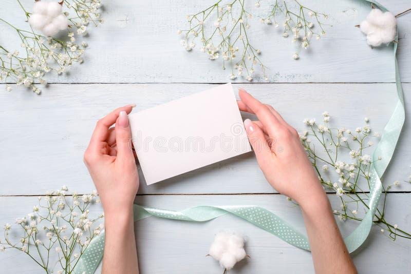 Hände, die Karte des leeren Papiers auf hellblauem hölzernem Schreibtisch mit Blumen halten Zarte Grußkarte für den Tag der Fraue stockfotos