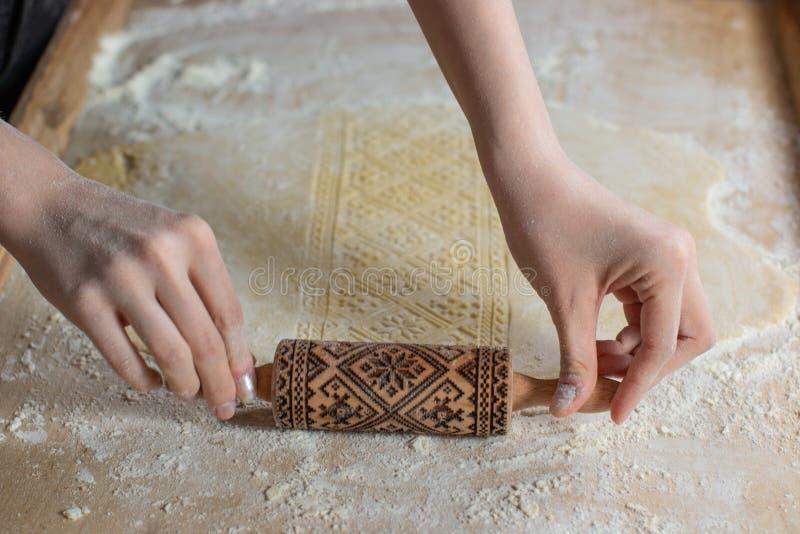 Hände, die Teig mit einem Prägungsnudelholz, auf einem hölzernen Hintergrund rollen lizenzfreie stockbilder