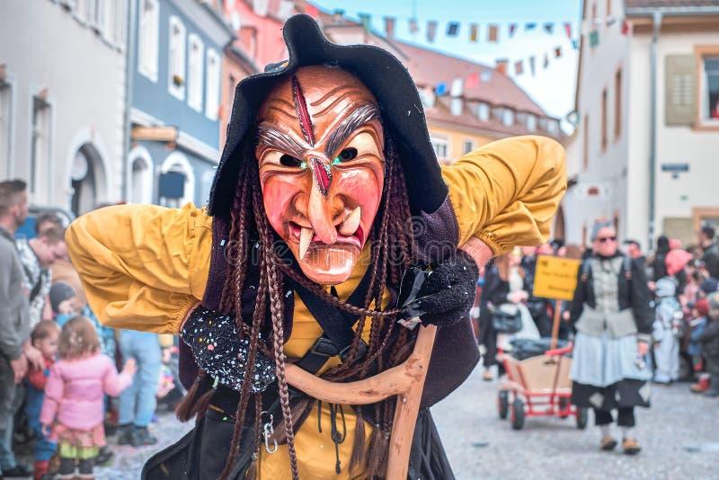 Hässliche Hexe in den gelben Robenblicken in die Kamera Straßenkarneval in Süd-Deutschland - Schwarzwald lizenzfreies stockfoto
