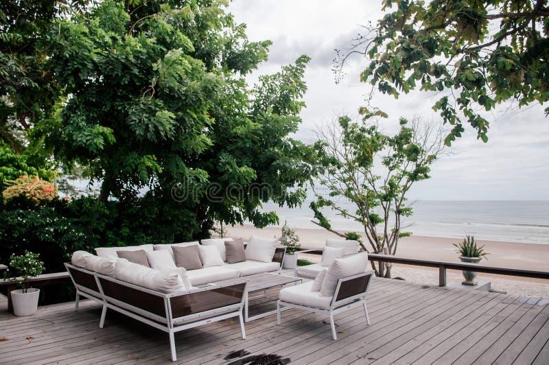Hölzerner Balkon der tropischen Ferien mit weißer Gewebesofacouch unter üppigem grünem Baum stockfotografie