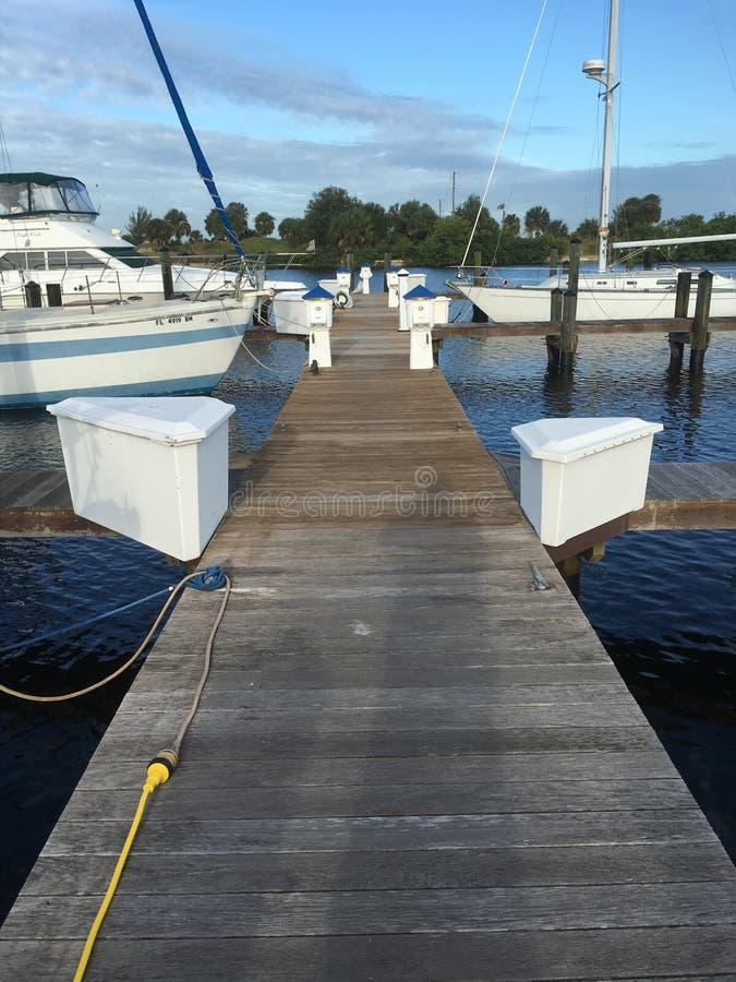 Hölzernes Dock und weiße Boots-blauer Himmel in Florida-Jachthafen lizenzfreies stockbild