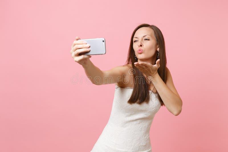 Hübsche Brautfrau in den weißen Heiratskleiderschlaglippen, den Luftkuß sendend und tun, das selfie nehmend geschossen am Handy stockbild
