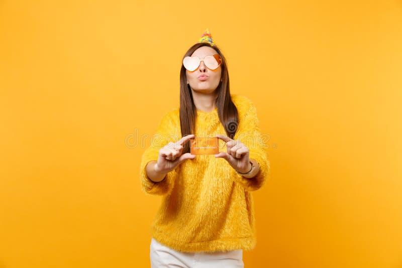 Hübsche junge Frau Holdingkreditkarte des orange Herzglasgeburtstagsfeierhutes in der Schlaglippen, Feiertag genießend lizenzfreie stockbilder