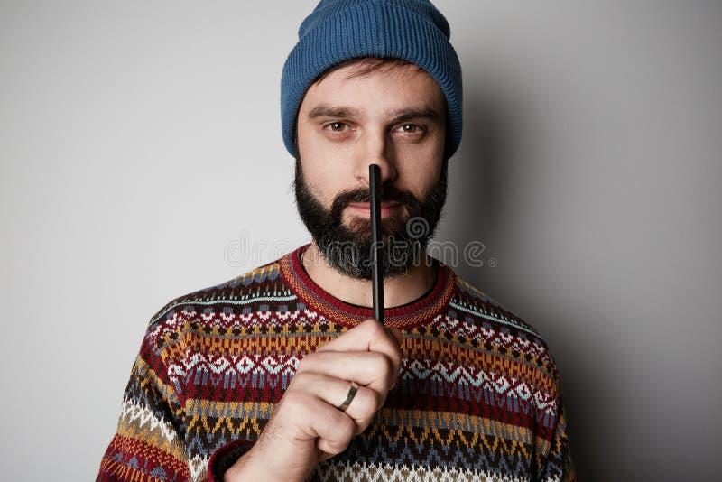Hübscher bärtiger Mann, der mit Stift an Ideen über weißem Hintergrund denkt stockbild