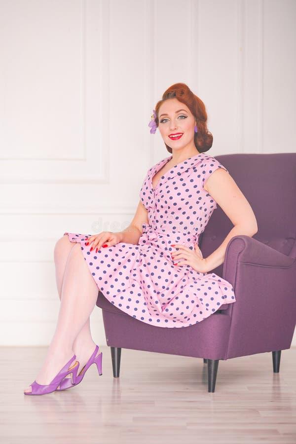 Hübscher redheaded Stift herauf die Frau, die rosa Tupfenkleid trägt und mit purpurrotem Lehnsessel auf weißem Hintergrund aufwir lizenzfreie stockfotos