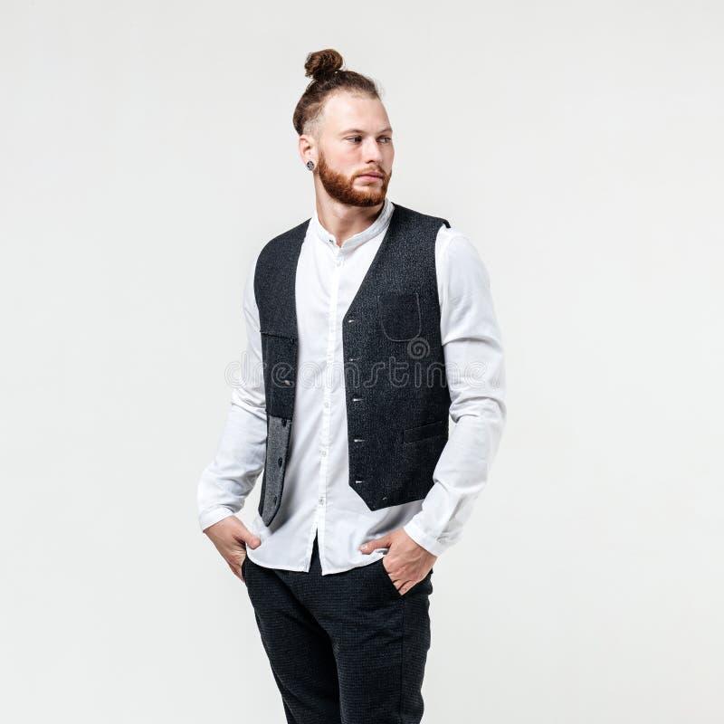Hübscher stilvoller Mann mit Bart- und Brötchenfrisur gekleidet in der grauen Weste über einem weißen Hemd und grauen Hosenhaltun lizenzfreies stockfoto