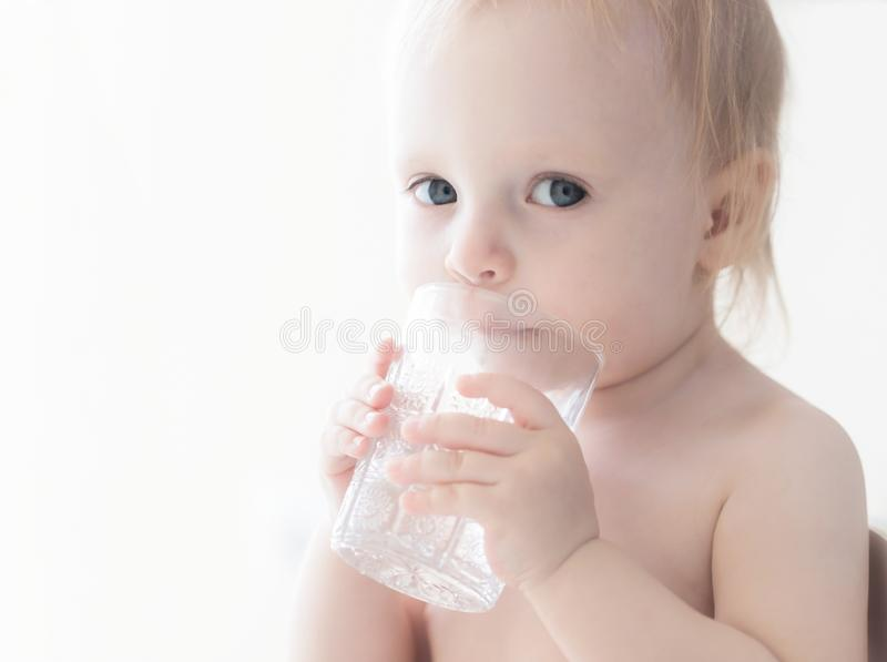 Hübsches ernstes süßes kleines Kind mit den Haselnussaugen des braunen Haares, die weg schauen, sitzend bei Tisch Trinkwasser vom stockfotos
