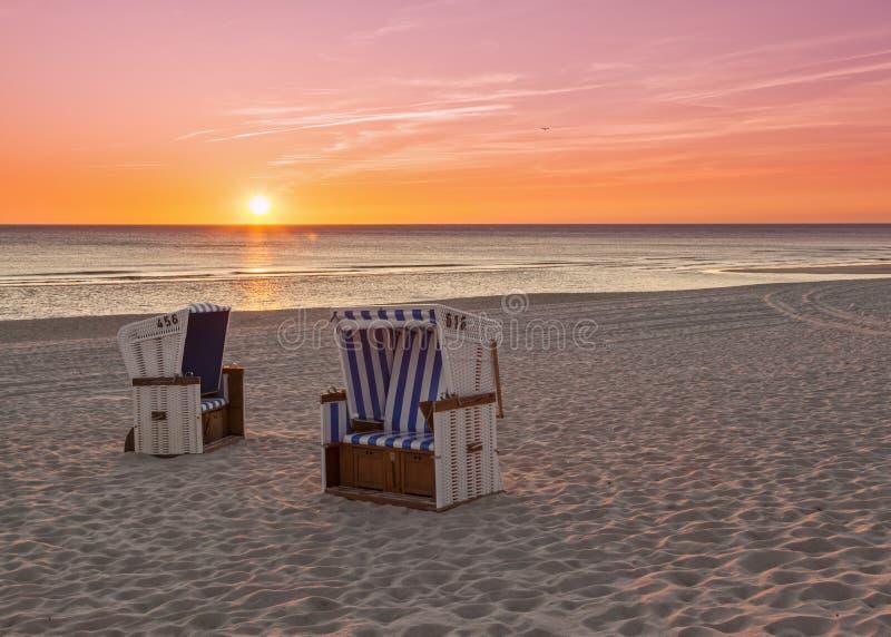 Hörnum Sylt - strandstolar på Nordsjön i solnedgång royaltyfria foton