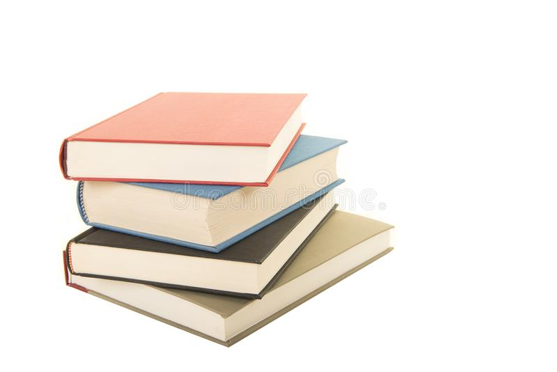 Häftklammer av böcker som ligger som ses ner från sidan som isoleras på en vit bakgrund royaltyfri bild