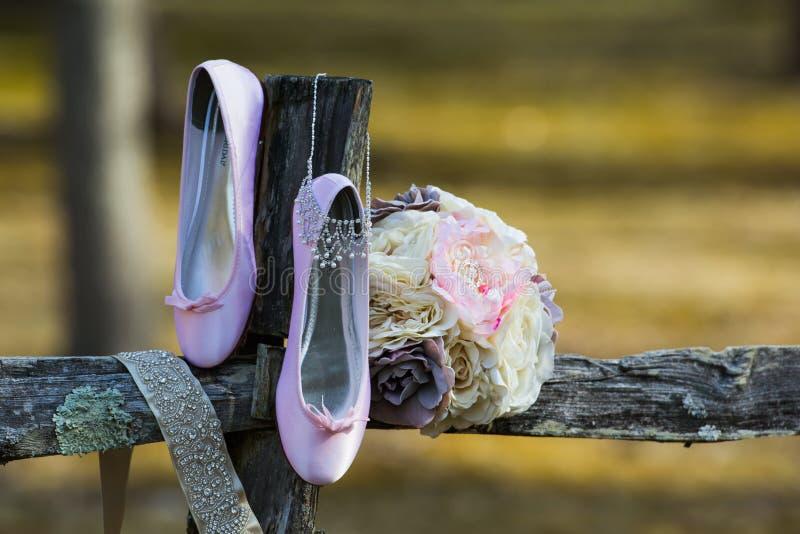 Häftklammermatare och bukett för tappning som rosa är ordnade på det gamla trästaketet royaltyfri foto