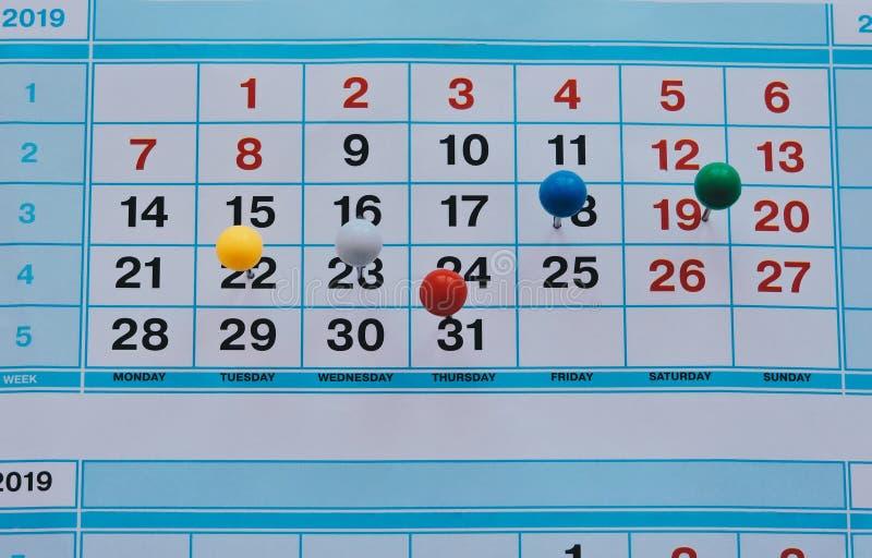 Häftstift i kalenderbegreppet för upptaget, arbetsutrymme Affärsmöteschema, loppplanläggning eller projektarbete royaltyfria bilder