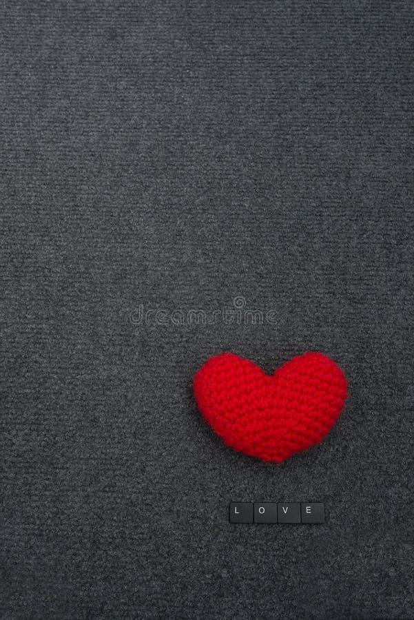 Häkeln Sie rotes Herz auf schwarzer Hintergrund- und Aufschriftliebe stockbild