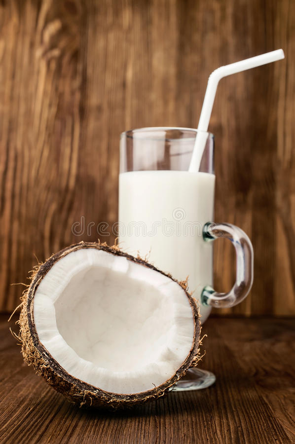 Hälfte der frischen Kokosnuss und der Kokosmilch in einem Glas lizenzfreies stockbild