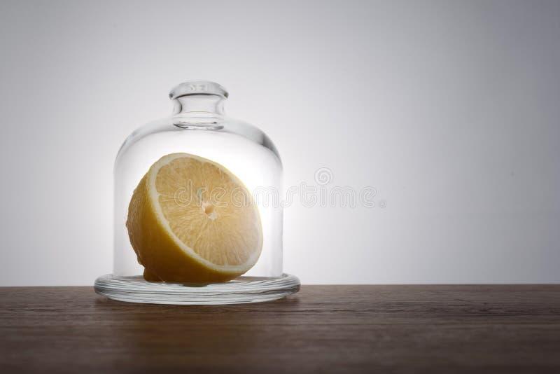 Hälfte der Zitrone in der Glasglasglocke auf Holztisch- und Lichthintergrund lizenzfreies stockfoto
