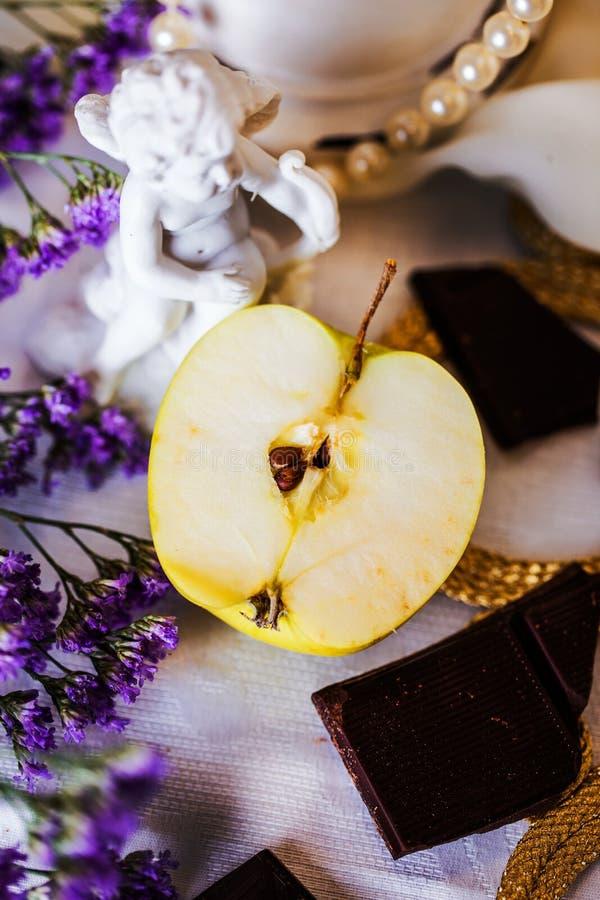 Hälfte ein Apfel in der schönen Stilllebenengelsfigürchen stockbild