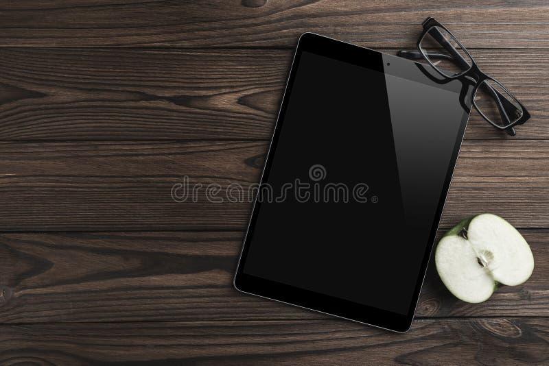 Hälfte ein Apfel, Tablet-PC, Brillen auf altem hölzernem Hintergrund Bürotisch Flache Lage, Draufsicht lizenzfreie stockbilder