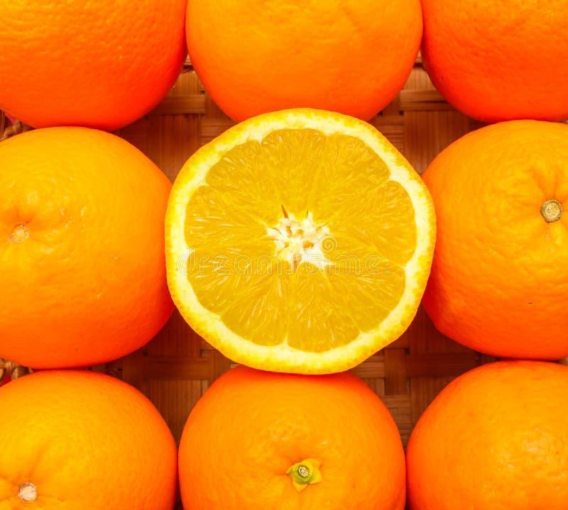 Hälfte einer frischen Orange in der Mitte anderer Orangen lizenzfreie stockbilder