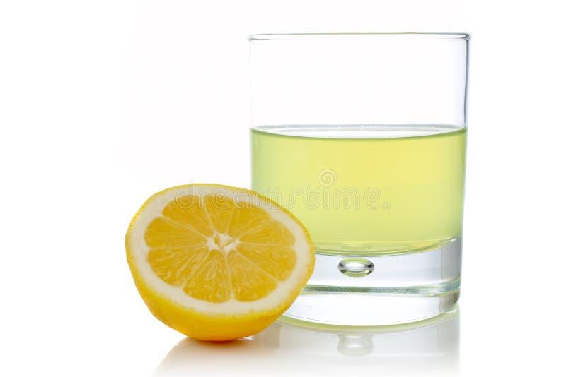 Hälfte und Glas der frischen Zitrone stockfotografie