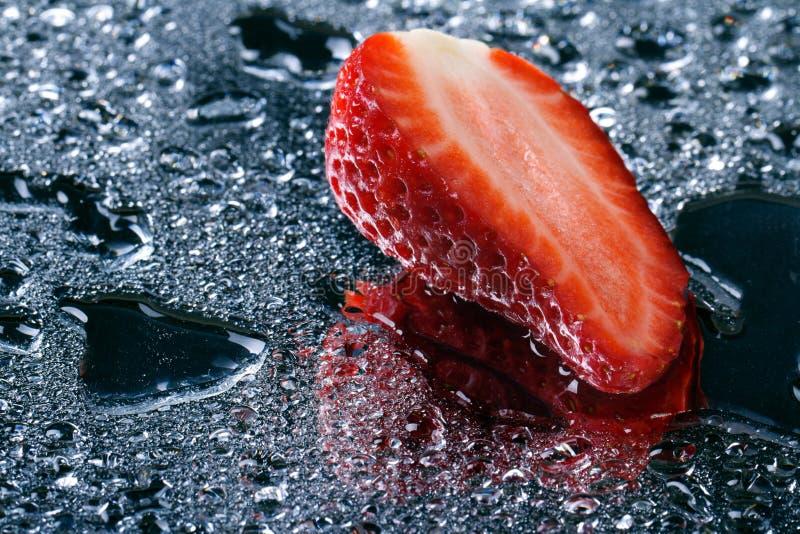 Hälfte von frischen Erdbeeren mit Wassertropfen stockbild