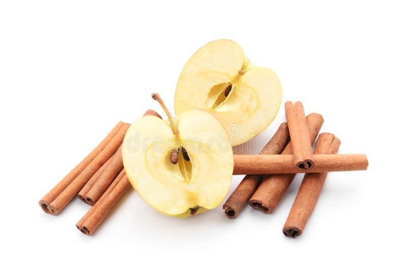 Hälften des frischen Apfels und der Zimtstangen auf weißem Hintergrund stockbild