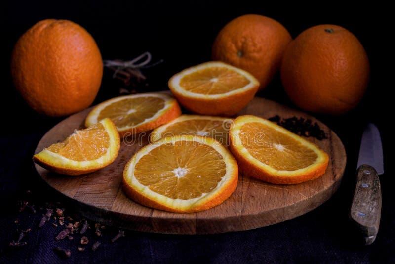Hälften und ganze Orangen auf hölzernem Brett über schwarzem Hintergrund, Abschluss oben lizenzfreie stockfotos