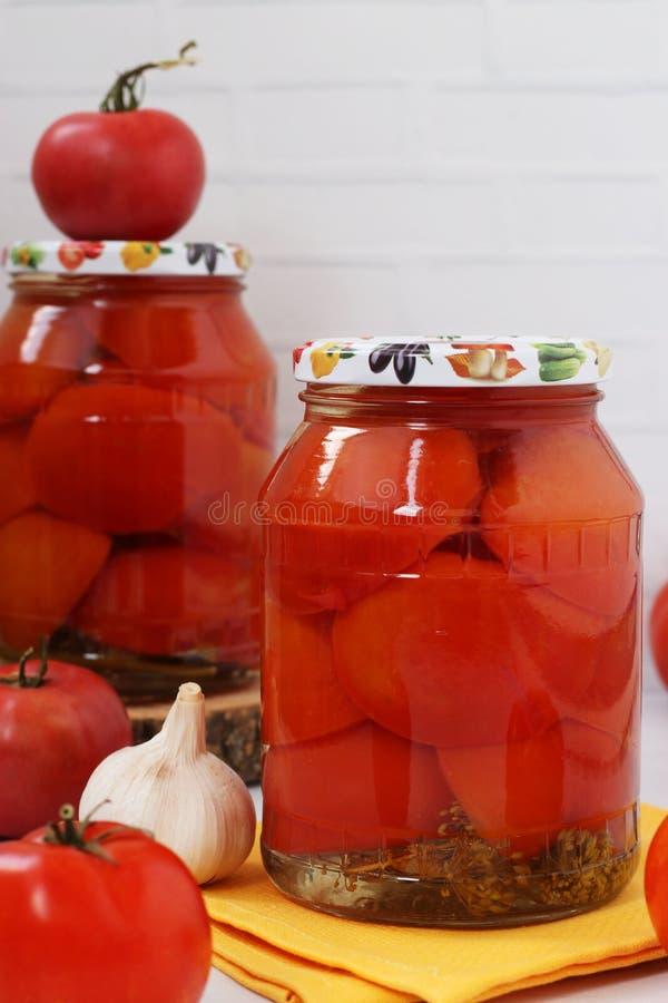 Hälften von den Tomaten, die in den Gläsern mariniert werden, werden auf einem weißen Hintergrund vereinbart lizenzfreies stockbild