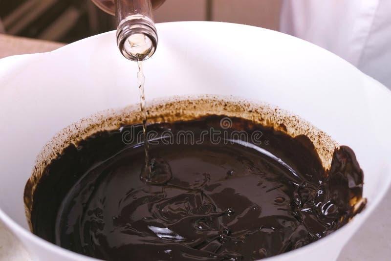 Häll och blanda glycerin till vätskemörk choklad i en vit bunke closen colors slappt övre siktsvatten för liljan royaltyfri foto