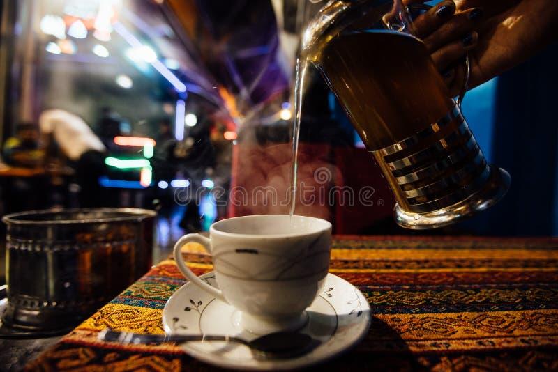 Häll te in i en kopp på ett gatakafé Strålar av ånga Arabisk anstrykning arkivfoton