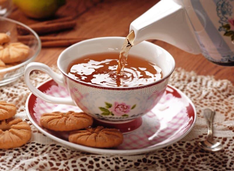 Häll teet in i koppen royaltyfria foton