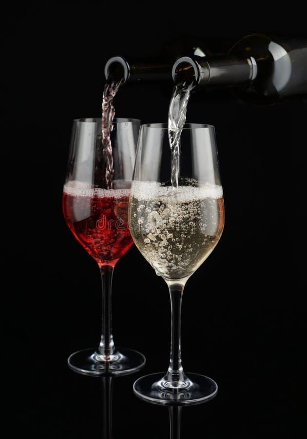 Hälla av vit och rött vin från flaskor in i exponeringsglas på mörk bakgrund royaltyfri fotografi