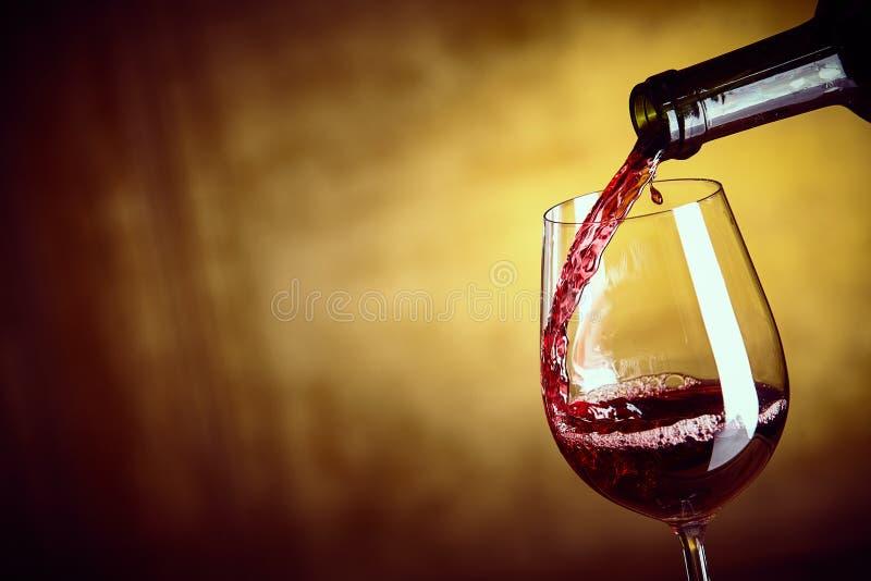 Hälla ett enkelt exponeringsglas av rött vin från en flaska fotografering för bildbyråer