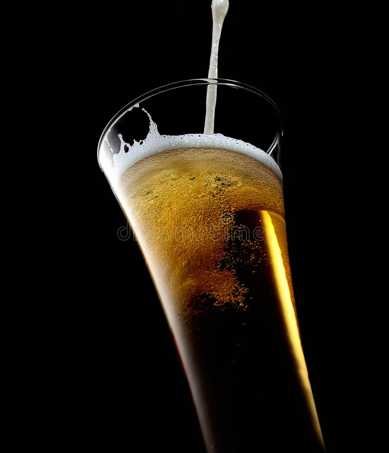 Hälla in i ett exponeringsglas av kallt skummande öl på en svart bakgrund royaltyfri bild