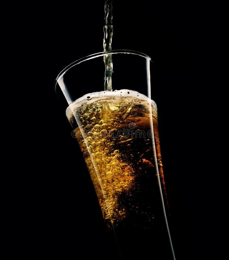 Hälla in i ett exponeringsglas av kallt skummande öl på en svart bakgrund royaltyfri foto