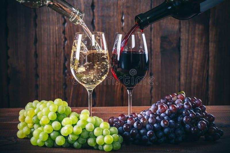 Hälla rött och vitt vin in i vinexponeringsglasen med en grupp av röda och vita druvor mot fotografering för bildbyråer