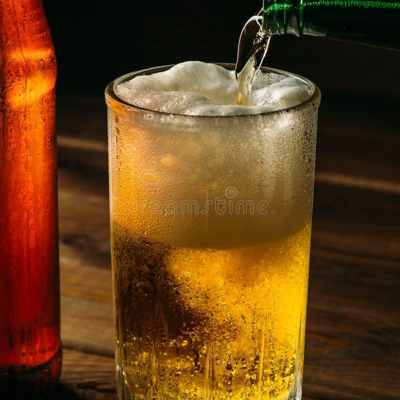 Hälla skumma öl in i exponeringsglas råna med droppar nära bootle för kallt öl, slut upp arkivbilder