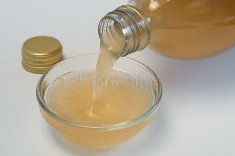 Hällande äppelcidervinäger från en flaska arkivfoto
