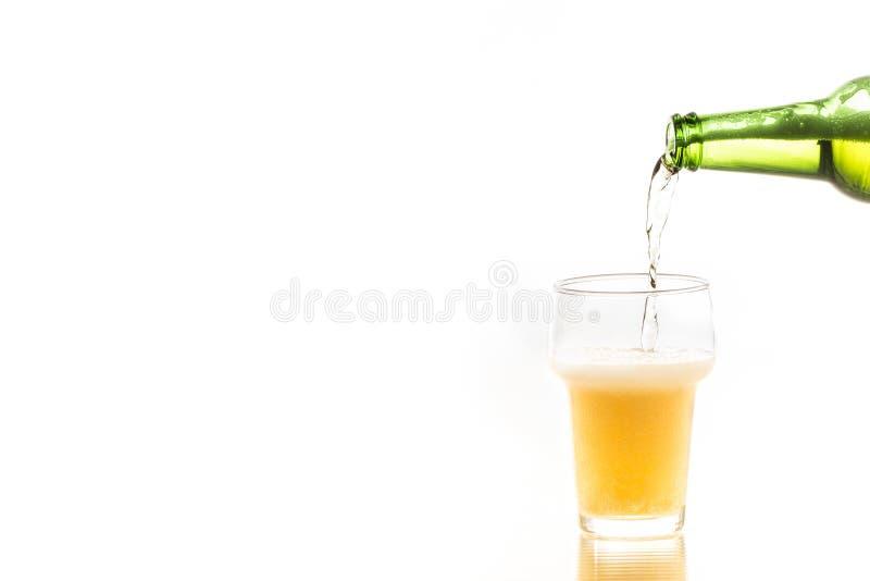 Hällande öl från flaskan royaltyfri bild