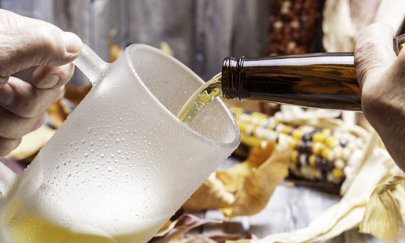 Hällande öl in i en råna. fotografering för bildbyråer