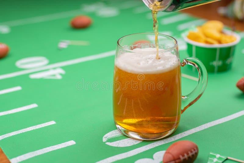 Hällande öl in i exponeringsglas rånar på tabellen som dekoreras för stor fotboll arkivbild
