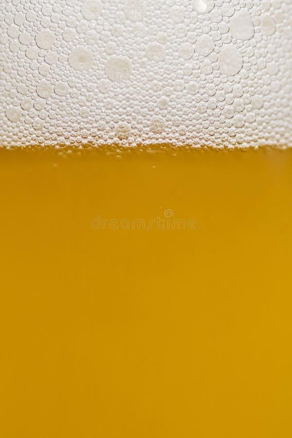 Hällande öl med bubblafradga i exponeringsglas för bakgrund på främre sikt Kalla öl för bakgrund med ölbubblor överst ett exponer royaltyfria bilder