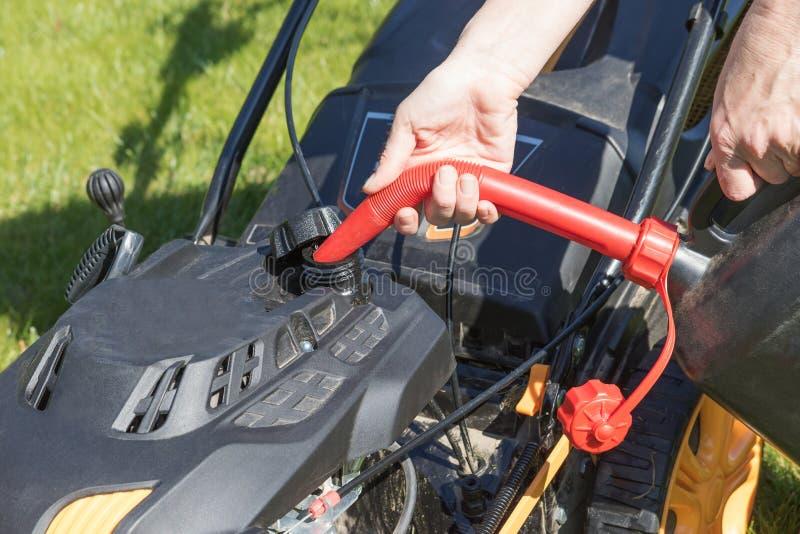 Hällande bensin in i gräsklipparen arkivfoton