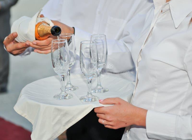Hällande champagne för elegant uppassare i exponeringsglas på en maträtt royaltyfri foto