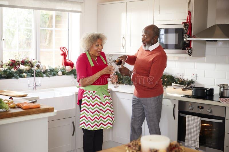 Hällande champagne för hög svart man för hans partner i köket, medan förbereda matställen på juldagen, selektiv fokus arkivfoto
